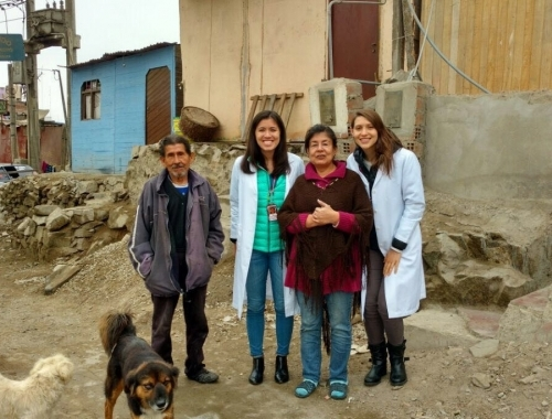 A Global Health Intern poses with a family in the field.