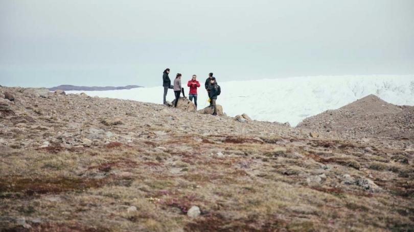 Students stand near a glacier in Greenland