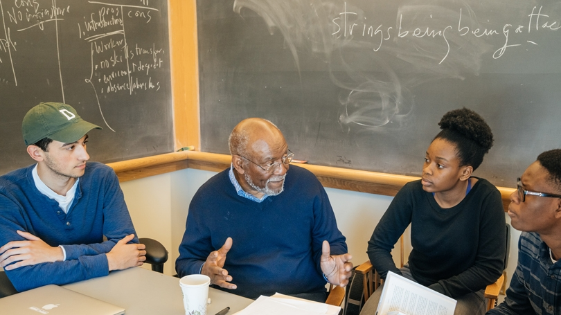 Students talk to Johnnie Carson in a classroom