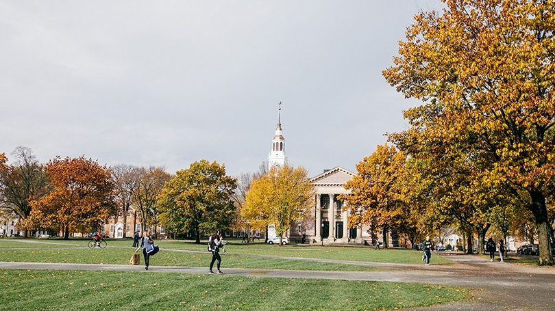 students walking across the Green with yellow foliage and Baker Tower in the background